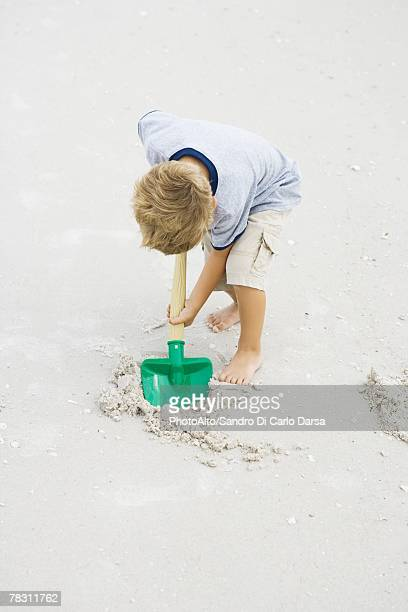 Young boy digging in sand with shovel, full length