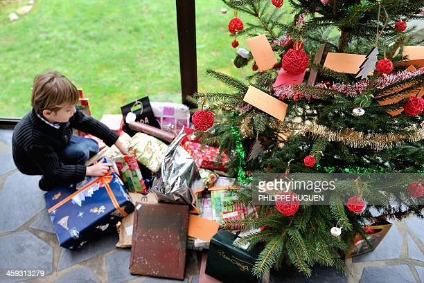 A young boy discovers his presents under the Christmas tree on December 25 2013 in Dinan northwestern France AFP PHOTO / PHILIPPE HUGUEN