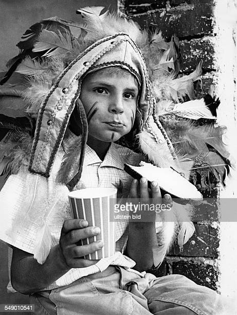 Young boy disguised as Indian eating a slice of bread and butter laste sixties