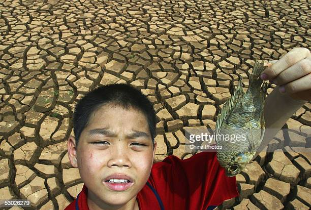 A young boy displays a dead fish from the bottom of a dried reservoir on June 2 2005 in Leizhou of western Guangdong Province southern China...