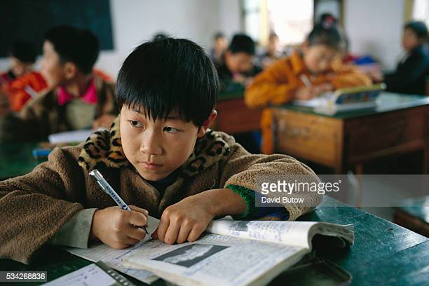 A young boy does his schoolwork in a small classroom in Anhui China