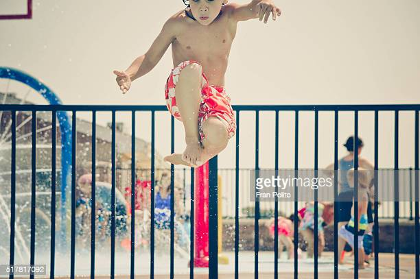 Young boy doing a cannon ball into the pool.