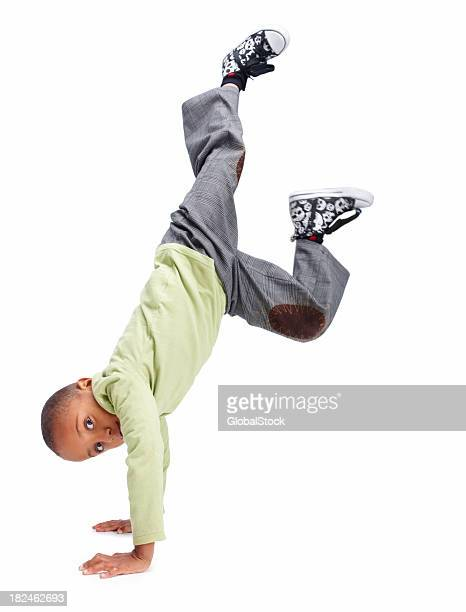 Young boy doing a handstand against white