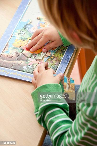 Young boy doing a jigsaw, elevated view