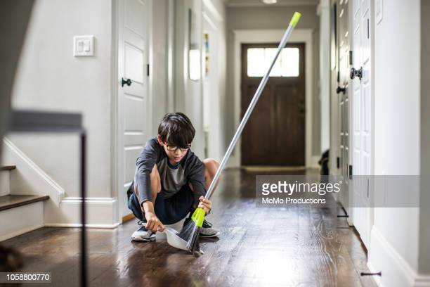 young boy doing cleaning and doing chores - haushaltsaufgabe stock-fotos und bilder