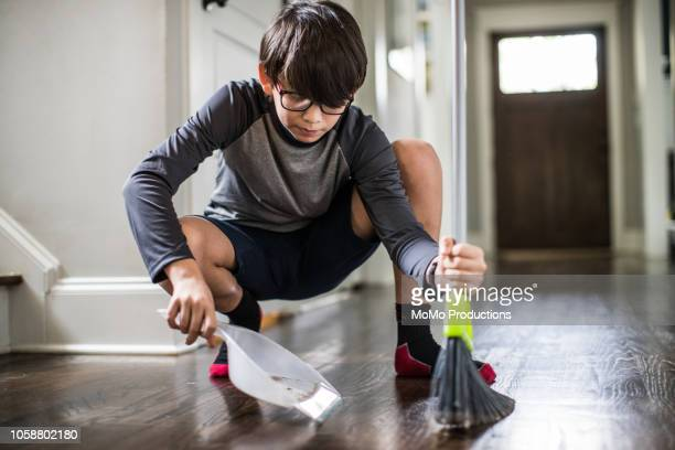 young boy doing cleaning and doing chores - dustpan and brush stock pictures, royalty-free photos & images