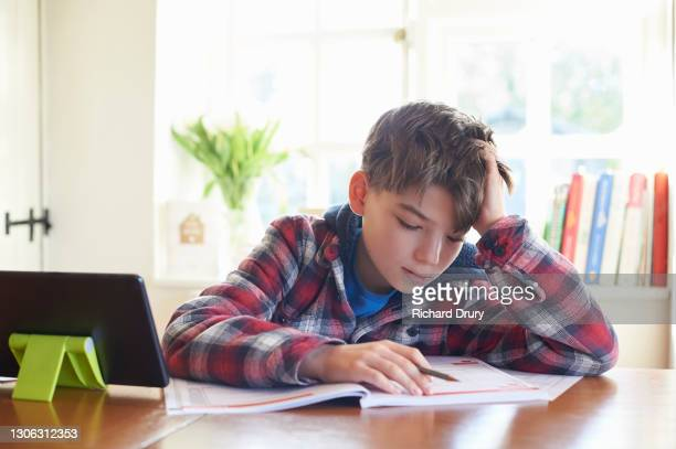 a young boy doing his homework at the kitchen table - richard drury stock pictures, royalty-free photos & images