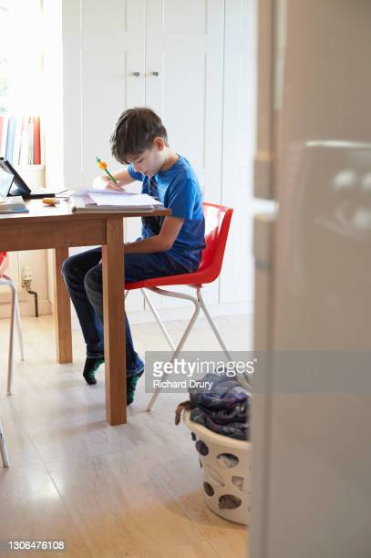 a young boy doing his homework at the kitchen table - real people stock pictures, royalty-free photos & images