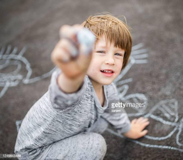 jonge jongen die het asfalt met een krijt krabbelt - alleen één jongen stockfoto's en -beelden