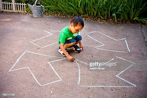 A young boy drawing a recycle sign on the ground.