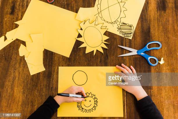 young boy drawing and cutting out yellow sun - linkshandig stockfoto's en -beelden