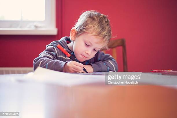 Young boy drawing at a table