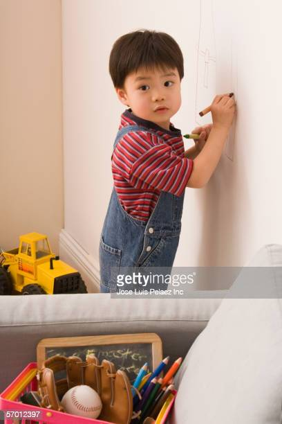 Young boy drawing on the wall