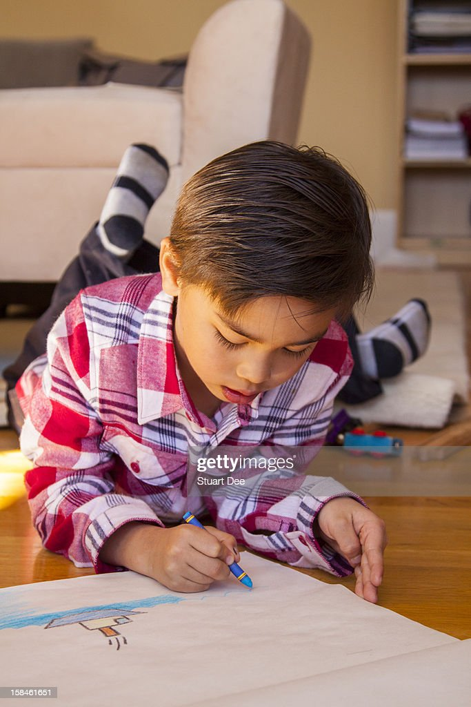 Young boy drawing with crayons, at home : Stock Photo
