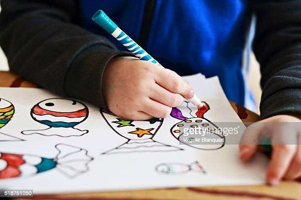 young boy draws and colors fishes for april fool's day. 31st march 2016 - poisson avril photos et images de collection