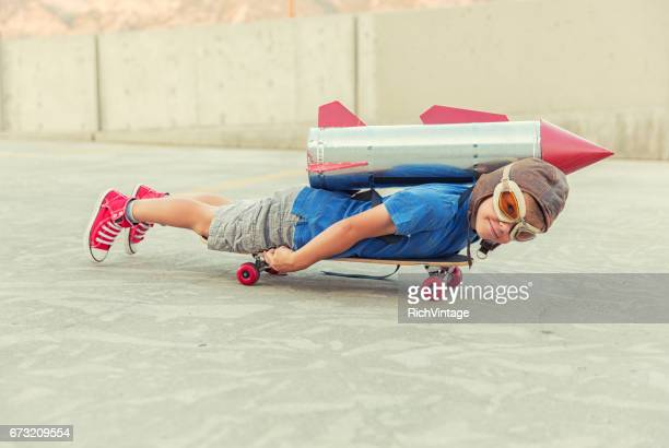 young boy dreams of flying with rocket - practical joke stock photos and pictures