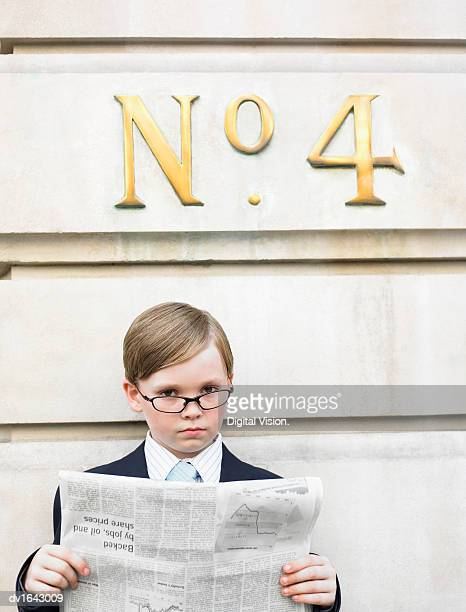 Young Boy Dressed as a Businessman Reads a Financial Newspaper Below a Street Number Sign