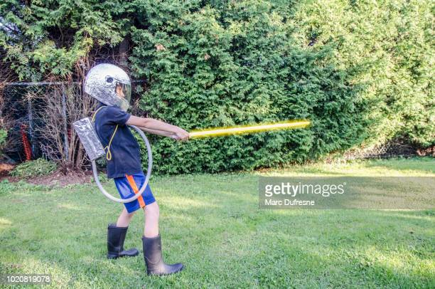 young boy dressed as an astronaut in the backyard during summer day - lightsaber stock pictures, royalty-free photos & images