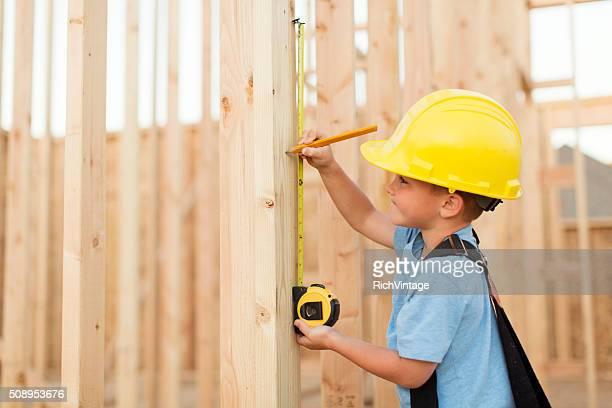 Jeune garçon habillé en tant que charpentier avec ruban à mesurer