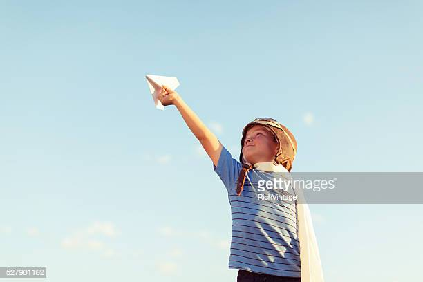 Young Boy Dressed as Pilot Flies Paper Airplane