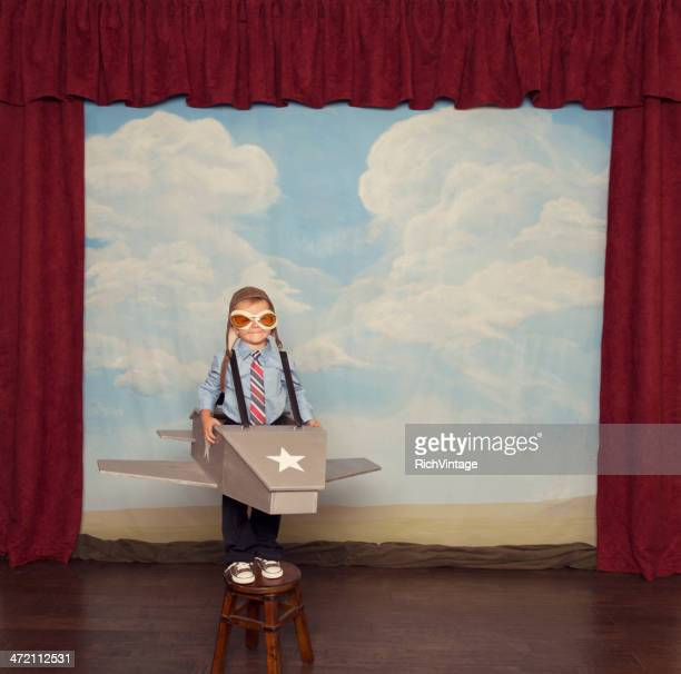 Young Boy Dressed as Pilot in Toy Airplane