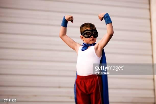 Jeune garçon déguisé en se plie Supehero Biceps