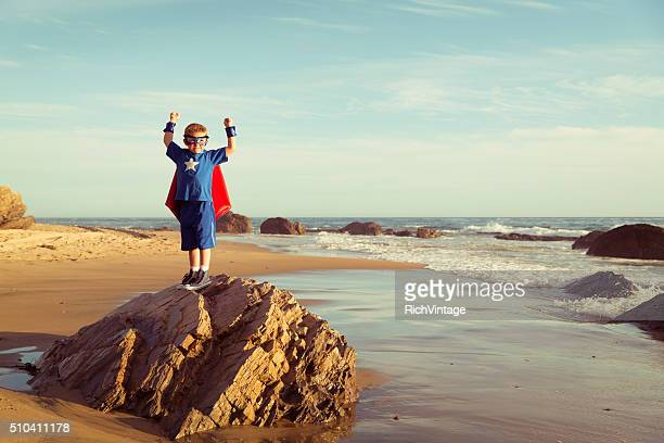 Young Boy Dressed as Superhero flexes Muscles on Beach