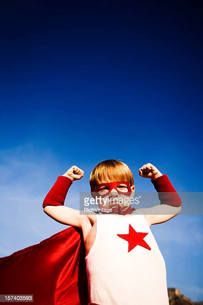 Young Boy Dressed as Superhero flexes Muscles