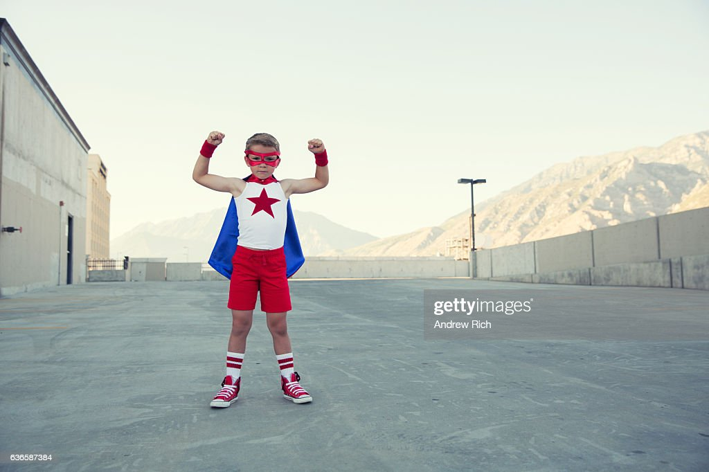 Young Boy Dressed as Superhero Flexes Muscles : Stock Photo