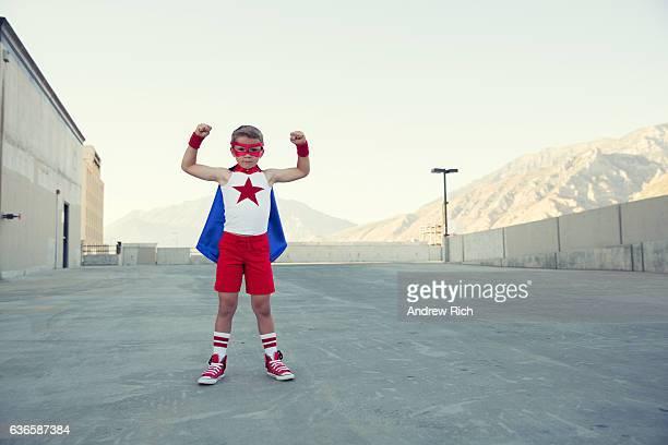 Junge gekleidet wie Superhelden passt Muskeln