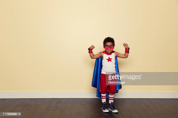 young boy dressed as superhero - flexing muscles stock pictures, royalty-free photos & images