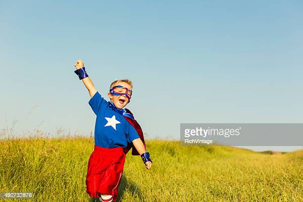 young boy dressed as superhero raises arm - superhero stock pictures, royalty-free photos & images