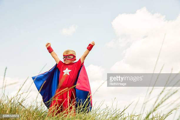 young boy dressed as superhero raises arms in park - cape garment stock photos and pictures