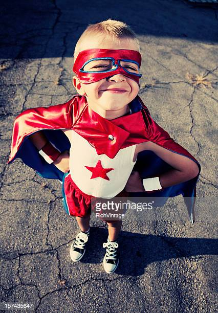 Young Boy Dressed as Superhero Smiles on Blacktop