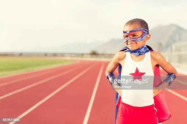 Young Boy Dressed as Superhero Stands on Running Track