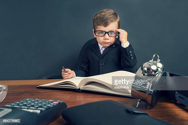 young boy dressed in suit working at desk. - bossy stock pictures, royalty-free photos & images