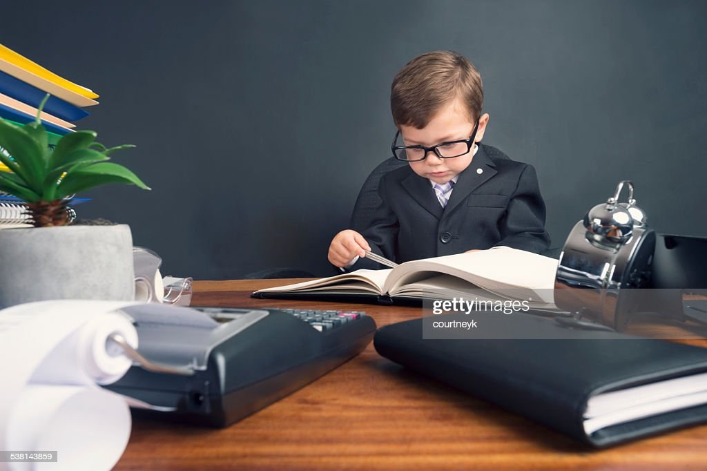 Jeune garçon habillé en costume travaillant au bureau pour