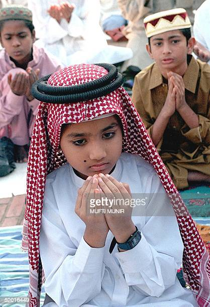 Young boy dressed in traditional Arabian fashion prays to the almighty 30 January at Bangladesh's Baitul Mukarram National mosque during...