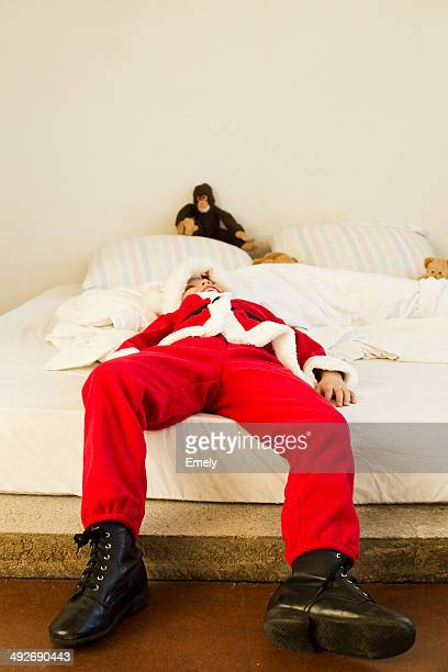 Young boy dressed up as santa claus lying on bed