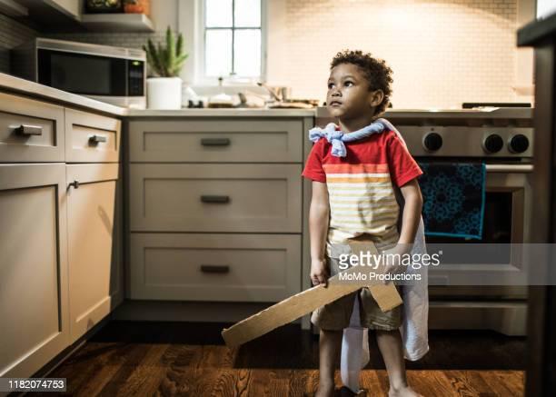 young boy (3 yrs) dressed up in cape in kitchen - seulement des enfants photos et images de collection