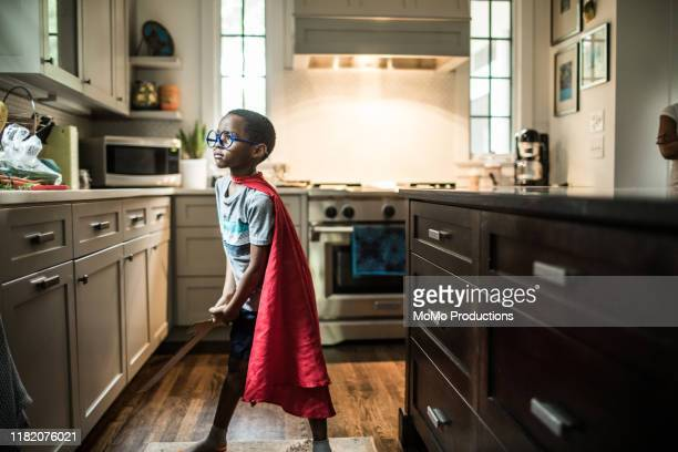 young boy (6 yrs) dressed up in cape in kitchen - superhero stock pictures, royalty-free photos & images