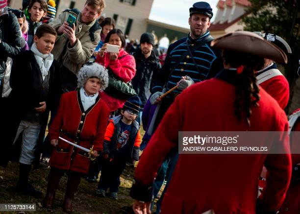 A young boy dressed up in period clothes watches reenactors play drums as part of Presidents day events at George Washingtons' Mount Vernon estate in...