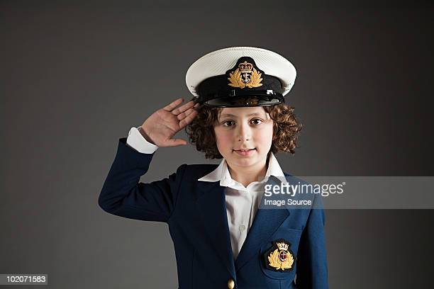 Young boy dressed up in sailor outfit, saluting