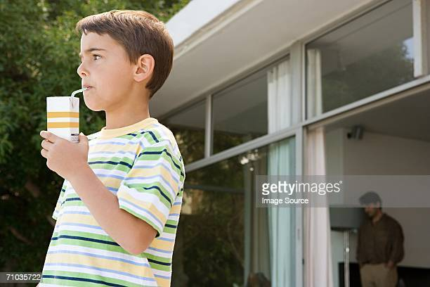 young boy drinking a carton of orange juice - juice carton stock photos and pictures