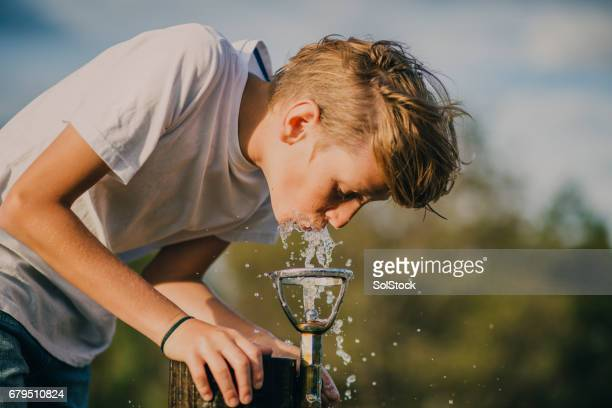 young boy drinking from a water fountain - fountain stock pictures, royalty-free photos & images