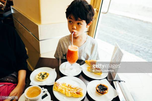 young boy drinking juice during breakfast - peter lourenco stock pictures, royalty-free photos & images