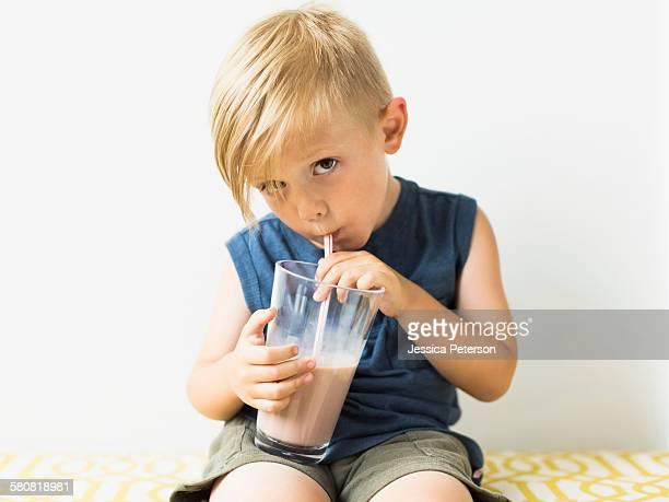 Young boy (2-3) drinking milkshake