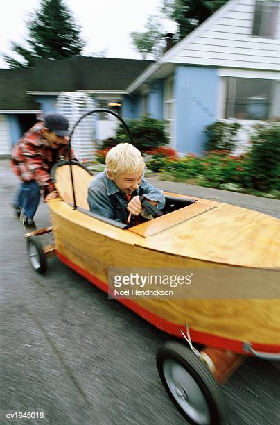 Young Boy Drives a Wooden Toy Boat on a Driveway Outside His House, Pushed Along by His Friend