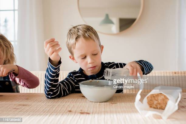 young boy during milk on his breakfast at home before school - breakfast cartoon stock pictures, royalty-free photos & images