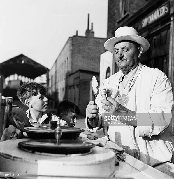 A young boy eagerly awaits his cornet from an street ice cream seller London England 1949